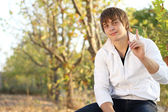 Attention! Handsome man sitting on the bench in autumn park — Stock Photo