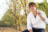 Pozor! pohledný muž sedí na lavičce v podzimním parku — Stock fotografie