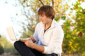 Young Man sitting in a bench with a laptop computer, autumn — Stock Photo