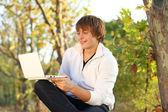 Happy man work at the laptop, outdoors autumn — Stock Photo