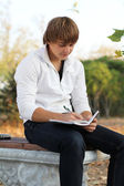Young man write poetry, autumn outdoors — Stock Photo