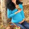 Beautiful pregnant woman with red apple, autumn outdoors — Stock Photo