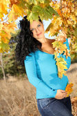 Pregnant woman caressing her belly over autumn park, outdoors — Stock Photo