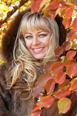 Portrait of pretty cheerful middle aged blonde woman over autumn — Stock Photo