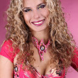 Happy smiling belly dancer girl with curly blond hair over ping - Stock Photo