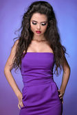 Beautiful fashionable brunette woman over violet — Stock Photo
