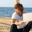 Smiling man with laptop outdoor on beach, outdoors — Stock Photo #7919525