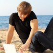 Business young guy working at laptop over beach — Stock Photo