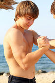 Arm-wrestling on beach outdoors — Stock Photo