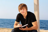 Attractive young man with writing pad on the beach — Stock Photo