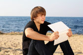 Thinking guy with laptop looking away on a beach — Stock Photo