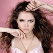 Fashion girl with perfect skin with long curly hairs over pink - Foto de Stock  