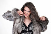 Fashion coquettish girl in fur coat isolated on white background — Stock Photo