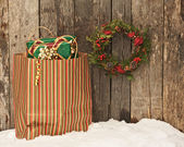 Wreath and bag with Christmas gifts on snow. — Stock Photo