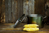 Corn ready to go into the pot on wood. — Stock Photo