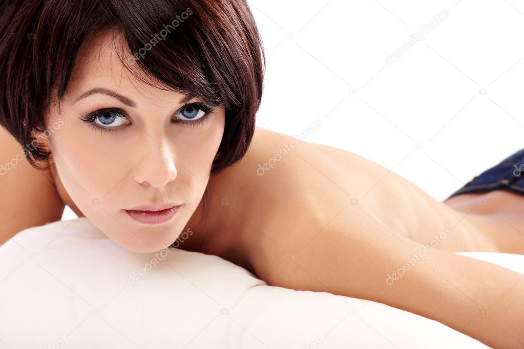 Closeup portrait of a young brunette woman lying in bed — Stock Photo #7486502
