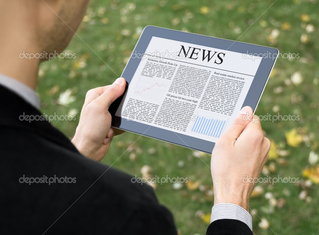 Businessman reading news on digital tablet at park.  Stock Photo #7591913