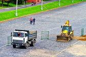 Bulldozer en vrachtwagen op de weg — Stockfoto