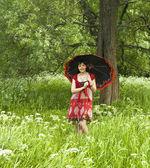 Mulher de vestido vermelho com guarda-chuva preto — Fotografia Stock