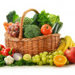 图库照片: Composition with vegetables and fruits in wicker basket isolated