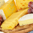 Composition with pieces of cheese on breadboard - Stock Photo