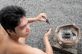 Asian man light coal stove — Stock Photo