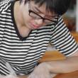 Asian thai chinese smiled smart man with glasses writing — Stock Photo
