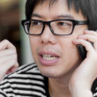 Stock Photo: Asian thai chinese smiled smart man with glasses talking telepho