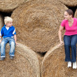 Young woman with his son on the hay bales — Stock Photo