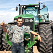 Farmer with tractor showing OK sign - Foto Stock
