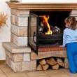 Stock Photo: Small girl warms by fireplace