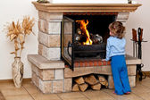Small girl warms by the fireplace — Stock Photo