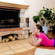 Stock Photo: Beautiful girl warms by fireplace