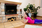Beautiful girl warms by the fireplace — Stock Photo