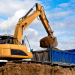 Stock Photo: Backhoe loading dump truck