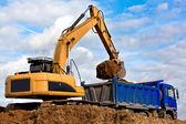 Traktorgrävare laddar en dump truck — Stockfoto