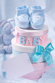 Little baby booties and gift boxes — Stock Photo