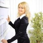 Young happy businesswoman near shelf with folders — Stock Photo #6774197