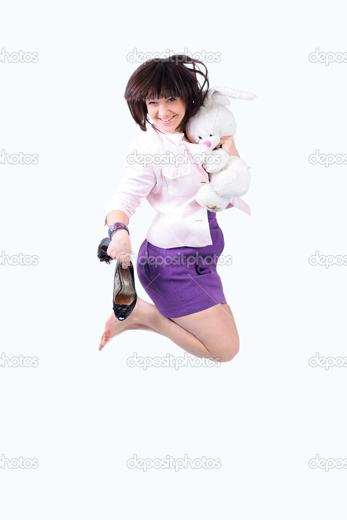 Young beautiful  woman jumping in joy with plush rabbit and black shoes in her arm, isolated over a white background  — Stock Photo #6864005