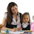 Foto de Stock  : Mother helping with homework to her daughter isolated