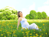 Pregnant woman sitting on meadow — Stock Photo
