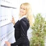 Young happy businesswoman near shelf with folders — Stock Photo #7928588