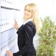 Stock Photo: Young happy businesswomnear shelf with folders
