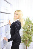 Young happy businesswoman near shelf with folders — Стоковое фото