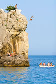 A man jumps off a cliff with a deep blue sea — Stock Photo