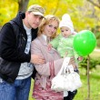 Stock Photo: Small beautiful girl with parent and with green air ball