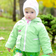 Small beautiful girl in green suit on green glade by autumn — Stock Photo