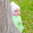 Stock Photo: Small beautiful girl in green suit on green glade by autumn peers because o