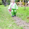 Small girl walks on autumn lane in wood — Stock Photo