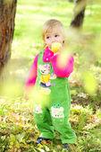 Liten vacker flicka på grön ört av hösten — Stockfoto